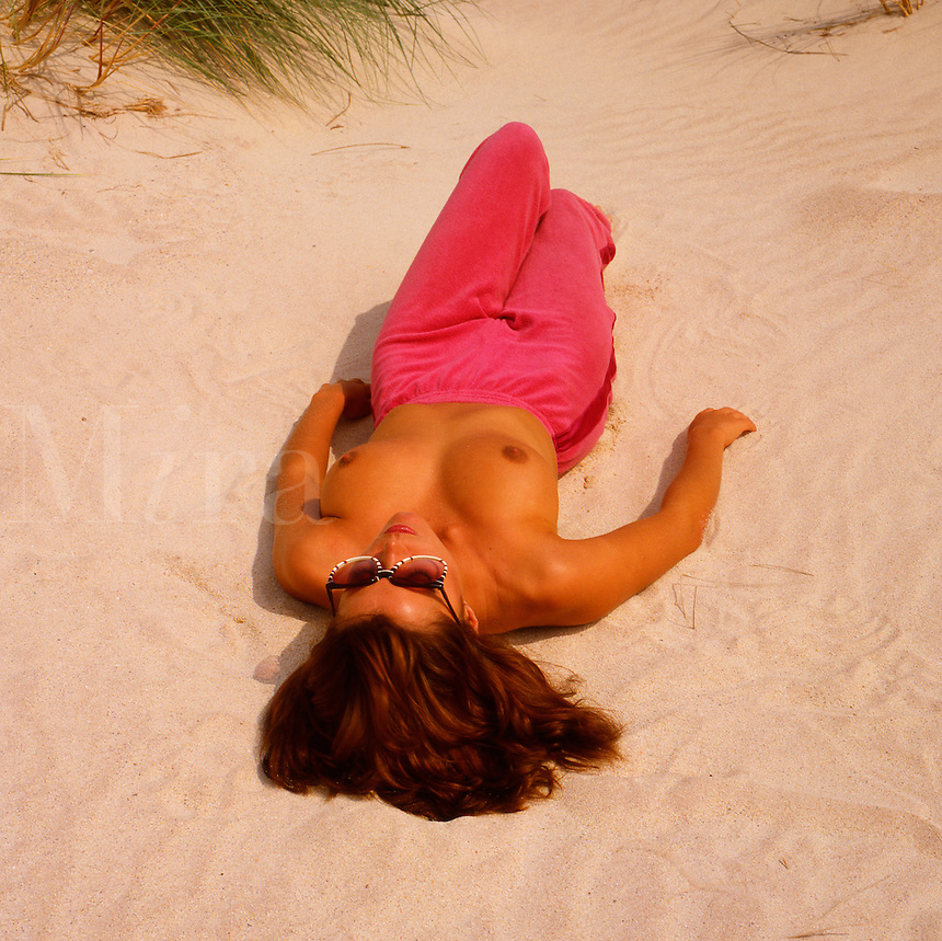 Young woman sunbathing topless on beach.