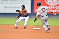 """Asheville Tourists shortstop Freudis Nova (7) fields the ball during an attempted steal from hard charging Kyle Stowers (37) during a game against the Aberdeen IronBirds on June 20, 2021 at McCormick Field in Asheville, NC. Tourists players were wearing jerseys for the """"Yacumamas de Asheville"""", as part of Minor League Baseball's """"Copa de la Diversion"""". (Tony Farlow/Four Seam Images)"""