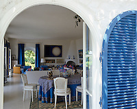 A view through an arched doorway into a blue and white open-plan living room
