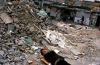 CHINA. Beijing. A man sleeps in the ruins of an old hutong (traditional home) in the central Qianmen district, destroyed to make may for new developments aimed at modernising the city for the 2008 Summer Olympics. 2005