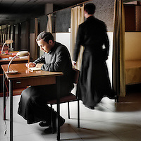 Juan Pablo Gallegos studies at a desk outside his cell as another priest walks past at the Legionaries of Christ seminar in Salamanca. Juan was born in Mexico. All correspondence of the seminarians is monitored by their superiors and they can only read books, press and listen to radio which is permitted by the seminary management. Their rooms are small and separated only by a glass partition which doesn't reach the ceiling, so there is little privacy. The Legion of Christ is a conservative Roman Catholic congregation whose members take vows of chastity, obedience and poverty.