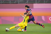 KASHIMA, JAPAN - AUGUST 5: Courtney Nevin #19 of Australia plays the ball under pressure from Carli Lloyd #10 of the United States during a game between Australia and USWNT at Kashima Soccer Stadium on August 5, 2021 in Kashima, Japan.