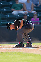 Umpire Takahito Matsuda cleans home plate during the South Atlantic League game between the Augusta GreenJackets and the Hickory Crawdads at L.P. Frans Stadium on May 11, 2014 in Hickory, North Carolina.  The GreenJackets defeated the Crawdads 9-4.  (Brian Westerholt/Four Seam Images)