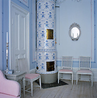 A Swedish wood burning stove in the corner of the master bedroom. The cylindrical kakelugnar, as it's called in Swedish, is covered with blue and white porcelain tiles