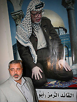 """prime minister in the government dismissed by President Mahmoud Abbas, walks in front of a picture of late President Yasser Arafat inside Arafat's house in Gaza June 30, 2007.""""photo by Fady Adwan"""""""