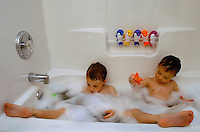 Brothers share playtime in a bubble bath.