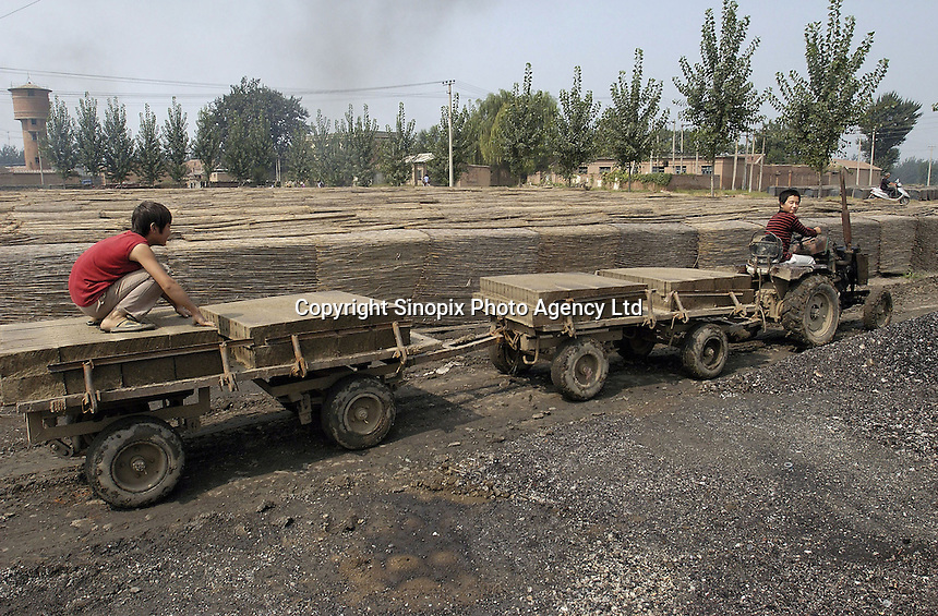 Two boys convey the clay bicks with a tractor at a brick factory in Bazhou, Hebei province, China..04-SEP-04