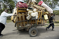 Kenya. Rift Valley province. Nakuru. 25.01.2008. Two black Kikuyu men, both IDPS, pulled a cart full of their belongings, chairs, tables, mattresses, pots, plastic containers and bottles,.... They are fleing from the inter-ethnic strife. Internally displaced persons (IDPs) are people forced to flee their homes but who, unlike refugees, remain within their country's borders. The Kikuyu are Kenya's most populous ethnic group. © 2008 Didier Ruef