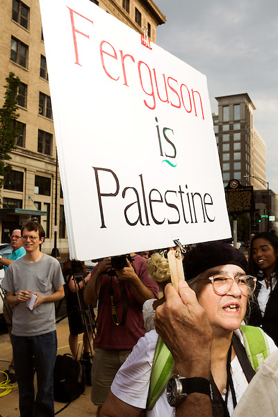 July 13, 2015. Winston Salem, North Carolina.<br />  A protestor carries a sign comparing the situation in Ferguson, Missouri to that of Palestine.<br />  A press conference was held outside the federal courthouse on the opening day of the North Carolina NAACP's case against Gov. Pat McCrory ( NC NAACP v. McCrory)<br />  The NC NAACP contests that HB 589 (Voter ID requirements) violate Section 2 of the Voting Rights Act (42 U.S.C. 1973) and the Fourteenth and Fifteenth Amendments of the Constitution.