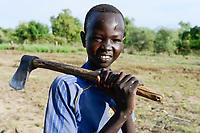 ETHIOPIA, Gambela, region Itang, Nuer village Pilual, boy Bhan 12 years old cutting firewood / AETHIOPIEN, Gambela, Region Itang, Dorf Pilual der Ethnie NUER, Hof von Herr Mun Kunen und Frau Neelam , sie sind vor dem Buergerkrieg aus dem Suedudan gefluechtet, Sohn Bhan 12 Jahre hackt Feuerholz