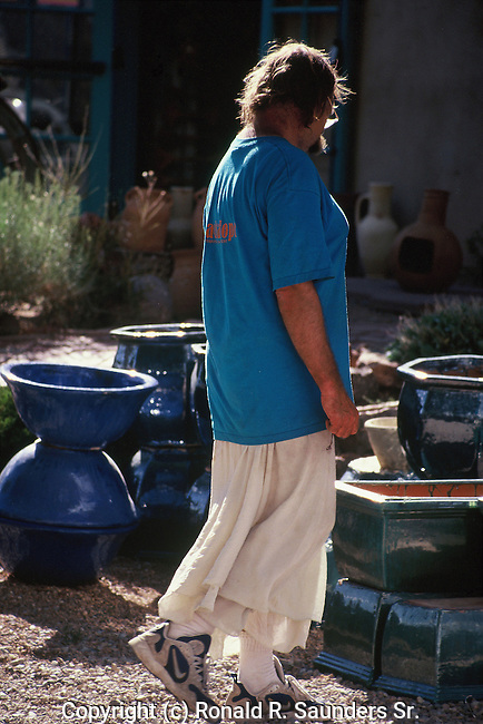 MAN IN SKIRT ADMIRES POTTERY