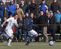 Brandeis defender Josh Hacunda (16) looks to pass as Williams forward Matt Kastner (20) closes. NCAA Division III Sectionals. Williams College (white) defeated Brandeis University (blue/white), 2-0, on Hitchcock Field at Amherst College on November 23, 2013.