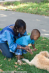 15 month old toddler boy outside with mother interested in pet dog reaching out to pet it vertical