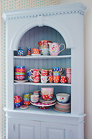 A collection of cheerfully coloured china is displayed in the corner cupboard in the kitchen