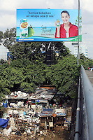 A large advertisement hangs above a slum community in central Jakarta.<br /> <br /> To license this image, please contact the National Geographic Creative Collection:<br /> <br /> Image ID:  1588066<br />  <br /> Email: natgeocreative@ngs.org<br /> <br /> Telephone: 202 857 7537 / Toll Free 800 434 2244<br /> <br /> National Geographic Creative<br /> 1145 17th St NW, Washington DC 20036
