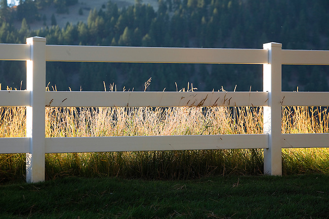 A white fence and grass along a rural road in Montana