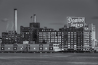 The Domino Sugars manufacturing plant and its iconic neon sign at twilight in Baltimore, Maryland.