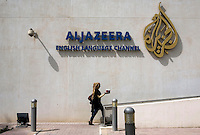 A woman carries coffee into the building of news channel Al Jazeera English in Doha.