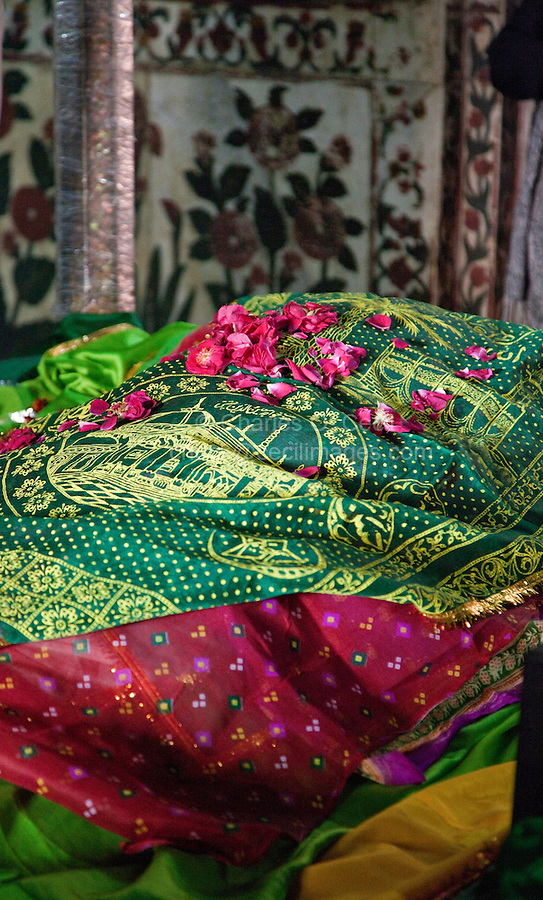 Fatehpur Sikri, Uttar Pradesh, India.  Inside the Mausoleum of Sheikh Salim Chishti.  Rose Petals and Fabric Offerings on the Grave.  Visitors often pray to the 16th-century holy man in hope of conceiving a child.