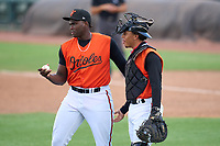 FCL Orioles Orange pitcher Alejandro Mendez (55) talks with catcher Ricardo Rivera (17) during a game against the FCL Pirates Gold on August 9, 2021 at Ed Smith Stadium in Sarasota, Florida.  (Mike Janes/Four Seam Images)