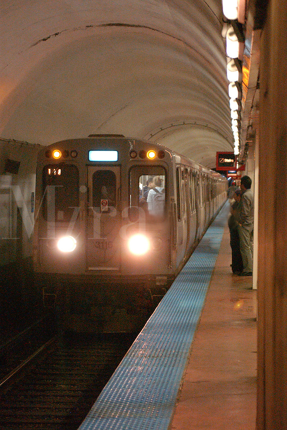 Chicago subway train stops at platform to pick up passengers.