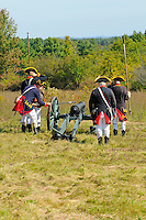Artilleryman of the 2nd Continental Artillery unit touches the linstock, holding a slow burning match at the end, to the priming powder in the vent hole of the cannon, at a Revolutionary War encampment on Bemis Heights, site of a major British defeat in October 1777, Saratoga National Historical Park, Stillwater, New York, USA.