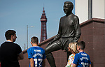Fans passing the statue to former player Jimmy Armfield outside Bloomfield Road stadium before Blackpool hosted Portsmouth in an English League One fixture. The match was proceeded by a protest by around 500 home fans against the club's controversial owners Owen Oyston, many of whom did not attend the game. The match was won by the visitors by 2-1 with two goals by Ronan Curtis watched by just 4,154 almost half of which were Portsmouth supporters.