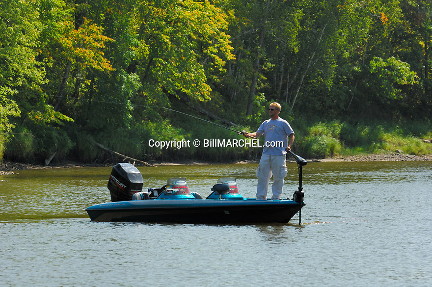 00416-027.05 Fishing (DIGITAL) Angler is casting from bass boat along rocky shoreline.  H3L1