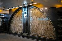 """Europe/ France/ Paris/75009: A la station de métro Richelieu-Drouot, située sur les lignes 8 et 9 se trouve dans la salle de correspondances le monument aux morts de la Compagnie du Métro Parisien, dû au ciseau de Carlo Sarrabezolles, inauguré en 1931.<br />  Ce monument en marbre noir est dédié à la mémoire des agents du chemin de fer métropolitain morts pour la France. La sculpture centrale est ornée d'une cariatide, qui soutient de ses bras levés la torsade de pierre qui l'entoure. Elle sépare en deux parties le demi-cercle à l'intérieur duquel sont inscrits les noms des agents du métropolitain disparus durant la Première Guerre mondiale. La base du monument porte les noms des champs de bataille de la Grande Guerre. Le mot « Libération » a été ajouté en bas à droite après la Seconde Guerre mondiale, afin de marquer la participation des agents du réseau à la Résistance.  //  Europe / France / Paris / 75009: At the Richelieu-Drouot metro station, located on lines 8 and 9, in the correspondence room is the monument to the dead of the Compagnie du Métro Parisien, due to the chisel of Carlo Sarrabezolles, inaugurated in 1931.<br />  This black marble monument is dedicated to the memory of the agents of the metropolitan railway who died for France. The central sculpture is adorned with a caryatid, which supports with its raised arms the stone twist which surrounds it. It separates into two parts the semicircle inside which are inscribed the names of the agents of the metropolitan who disappeared during the First World War. The base of the monument bears the names of the battlefields of the Great War. The word """"Liberation"""" was added at the bottom right after World War II, to mark the participation of network agents in the Resistance."""