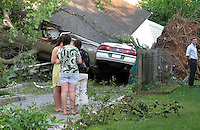 A car is buried under a large tree after a storm in New York.