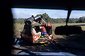 "Lolgorian, Kenya. Battered pick-up truck on muddy road with passengers, plastic drums on top, ""The True Taste of Kenya"" on back."