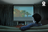 Woman watching movie at home on projection screen (Licence this image exclusively with Getty: http://www.gettyimages.com/detail/103810539 )