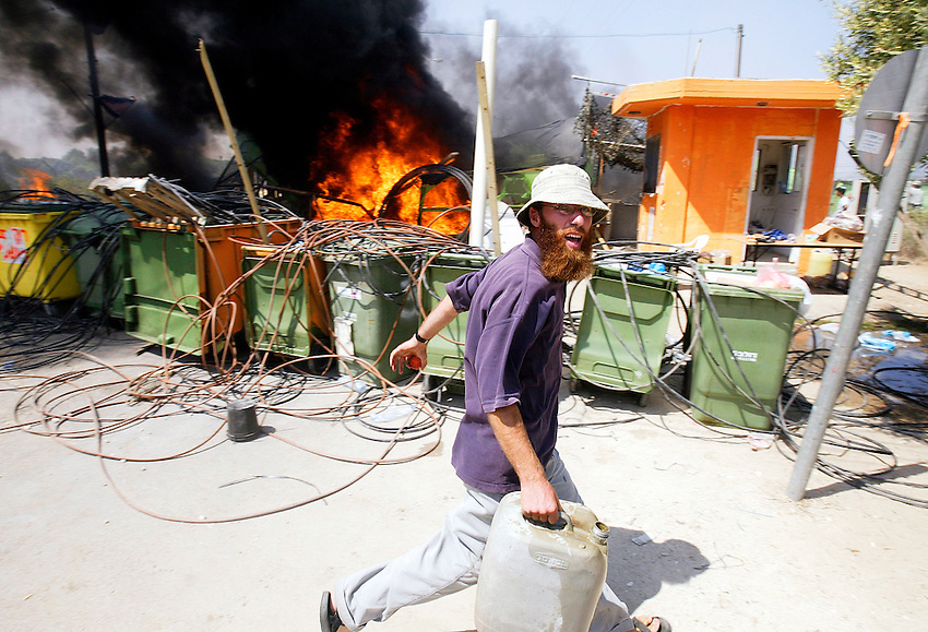 Crazed anti-disengagement activist runs with container of gasoline after lighting the main gate of the Netzer Khazani settlement ablaze as the Israeli Army arrives to physically remove all the residents as part of Israel's disengagement from the Gaza Strip.   GUSH KATIF, GAZA STRIP  8/18/05....