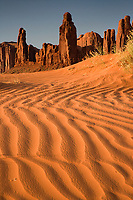 """A fine art Southwestern nature image of the Yei Bi Chei rock formations, one of the two more famous formations in Monument Valley, with sand patterns leading into the foreground.  The orange rock and sand take on a stronger orange tone in the late day sun.  This image pairs nicely with """"Totem Pole at Sunrise - Monument Valley.""""  The Yei Bi Chei formations are a classic symbol of the American Southwest.  It is said that Yei Bi Chei is a Navajo Spirit associated with the nine-day Navajo ceremony called """"Night Way,"""" held during the winter.  The rock formation supposedly resembles the fire dancers who appear on the last day of the ceremony.  The Yei Bi Chei formations are located in Monument Valley near the Totem Pole.  Monument Valley is a region of the Navajo Nation known as the Colorado Plateau characterized by clusters of sandstone buttes.  This area is located near the Arizona-Utah border, near the Four Corners area."""