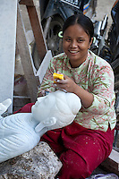 Myanmar, Burma, Mandalay.  Burmese Craftswoman Sanding and Polishing Buddha Carved from Stone.  Many are exported to China.