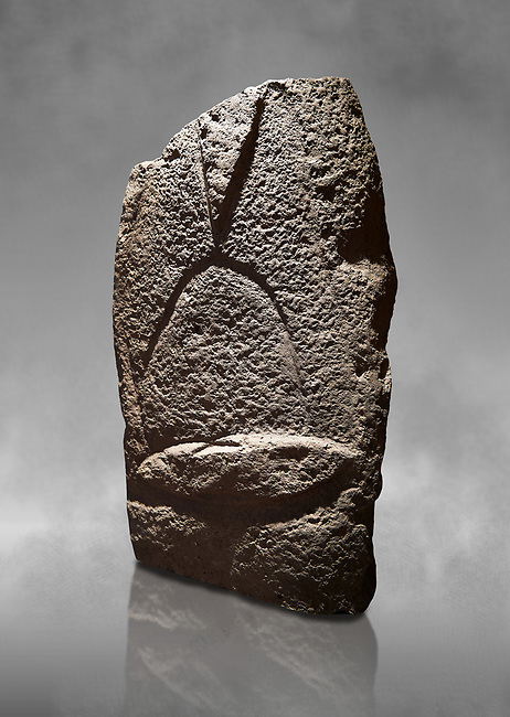 Late European Neolithic prehistoric Menhir standing stone with carvings on its face side. The representation of a stylalised male figure starts at the top with a long nose from which 2 eyebrows arch around the top of the stone. below this is a carving of a falling figure with head at the bottom and 2 curved arms encircling a body above. at the bottom is a carving of a dagger running horizontally across the menhir. Excavated from Cabamadau, Villa Sant' Antonia. Menhir Museum, Museo della Statuaria Prehistorica in Sardegna, Museum of Prehoistoric Sardinian Statues, Palazzo Aymerich, Laconi, Sardinia, Italy
