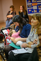 """A mother breastfeeding her baby at a conference.<br /> <br /> Image from the breastfeeding collection of the """"We Do It In Public"""" documentary photography picture library project: <br />  www.breastfeedinginpublic.co.uk<br /> <br /> <br /> Middlesex, England, UK<br /> 2016<br /> <br /> © Paul Carter / wdiip.co.uk"""
