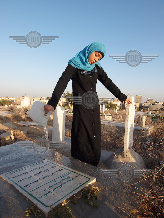 """Amira Al-Qerem (16) washes the grave of her father, sister and brother in Gaza City on October 26 2010. Amira was missing and presumed dead after she was injured by one of the same explosions that killed her father, brother and sister during the last days of the Israeli invasion of Gaza in 2009. She was found three days later, after her family thought they had buried her remains with those of the other three. She is one of the main subjects of the controversial documentary film """"Tears of Gaza"""" by director Vibeke Løkkeberg."""