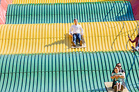 South Bend mayor and Democratic presidential candidate Pete Buttigieg rides the Giant Slide at the Iowa State Fair in Des Moines, Iowa, on Tues., Aug. 13, 2019.