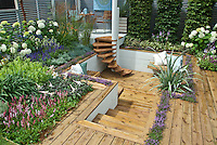 Flowers and herb interplanted in tiered levels sunken wooden deck, privacy walls, steeps, patio furniture, thymus thymes, hydrangeas, mixture of textures and shapes, beautiful.