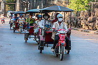 Cambodia.  Ankor Thom, South Gate.  Driving Tourists Back to their Hotels in Late Afternoon.  The figures lining the road on the right are asuras (demons).