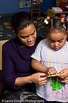 Education Preschool 3-4 year olds female teacher working with girl on lacing activity manipulatives vertical