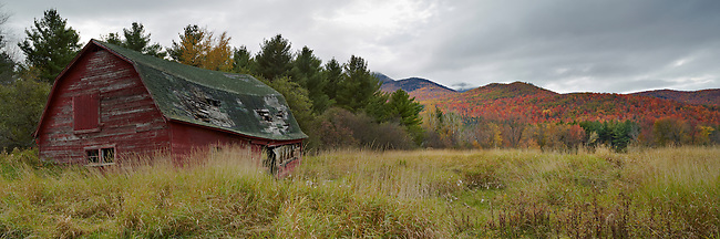 An Autumn view of an old barn in a field as seen from Rt. 73 looking towards the high peaks in the High Peaks Region of New York State's Adirondack Park.