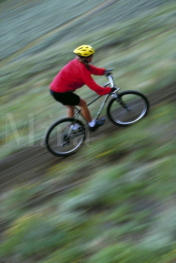 Woman mountain biking, blurred motion, Rocky Mountains, Colorado. Kim Clark (MR 671). Colorado.