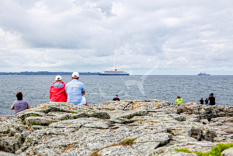 """the Queen Mary 2 passing Groix Island, on her way to Saint Nazaire for the start of the centennial Transat """"The Bridge 2017"""", a historic transatlantic race between her and a fleet of giant trimarans."""
