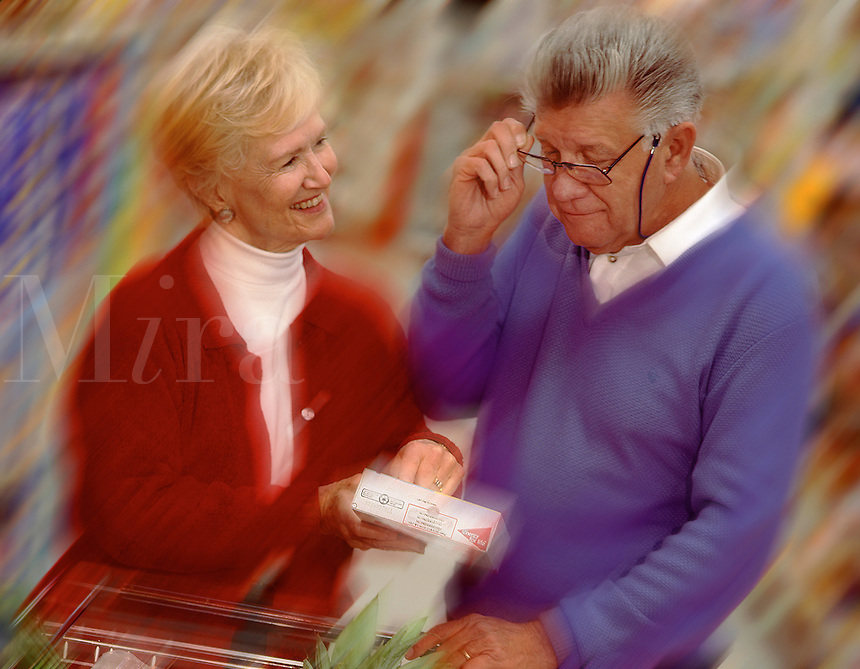 Senior couple grocery shopping, reading labels. .