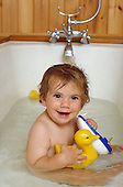A two-year old child plays with plastic ducks in the bath (posed by model).
