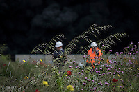 Picture shows some flowers on a field close to big clouds of dark smoke produced by piles of tyres burning in an uncontrolled dump near the town of Sesena, after a fire broke out early on May 13, 2016. A huge waste ground near Madrid where millions of tyres have been dumped was on fire today, releasing a thick black cloud of toxic fumes that officials worry could harm residents nearby. © Pedro ARMESTRE