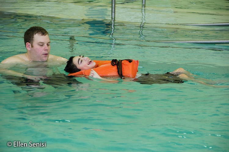 MR / Albany, NY.Langan School at Center for Disability Services .Ungraded private school which serves individuals with multiple disabilities.Teaching assistant helps non ambulatory student wearing life jacket float and swim while in the pool during gym class. Students in this class swim once a week as part of their physical education program. Boy: 11, cerebral palsy, expressive and receptive language delays.MR: Bro12, Gar7.© Ellen B. Senisi