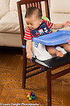 9 month old baby in infant seat strapped to chair leaning over to drop toy or to look at dropped toy, anticipating sound as toy hits the floor